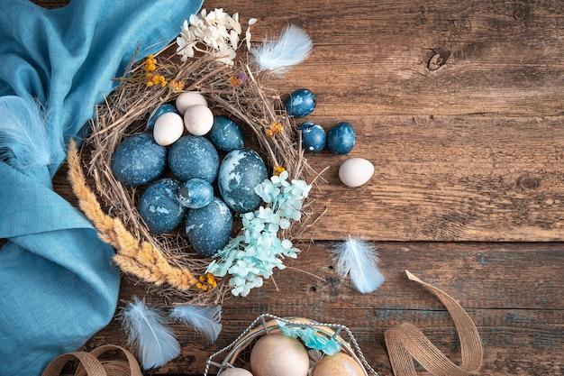 Piękna kompozycja wielkanocna z kolorowymi jajkami różnych typów w ptasim gnieździe.