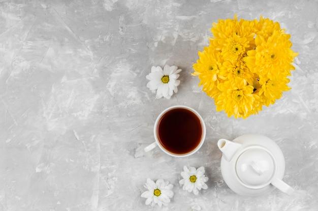 Piękna kompozycja wiosennych kwiatów z filiżanką herbaty i czajniczkiem
