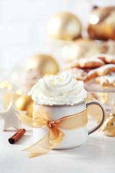 Piękna kompozycja z filiżanką cappuccino i świątecznymi ciasteczkami