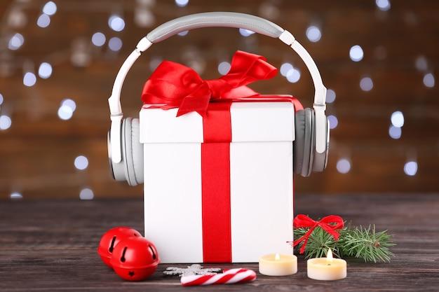 Piękna kompozycja z pudełkiem prezentowym i słuchawkami na stole przed niewyraźnymi światłami. koncepcja muzyki świątecznej