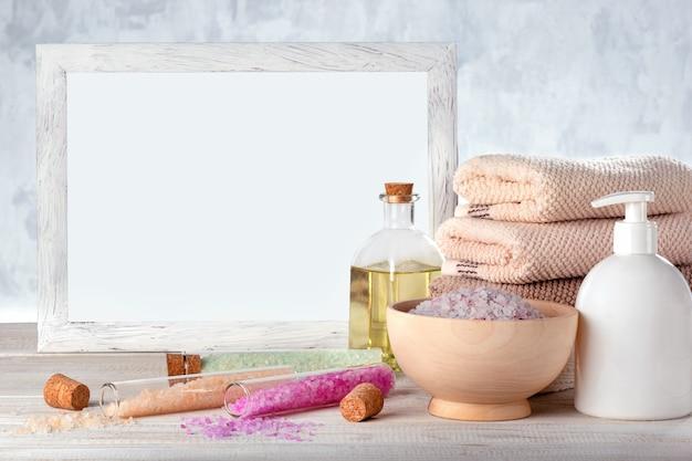 Piękna kompozycja z solą, balsamem, olejkiem, ręcznikiem i makietą białej ramy na drewnianym stole. koncepcja spa.