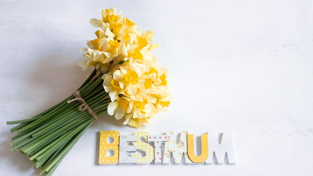 Piękna kompozycja z wiosennymi kwiatami na dzień mamy i drewnianym napisem best mum