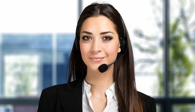 Piękna konsultantka call center w słuchawkach w jasnym biurze