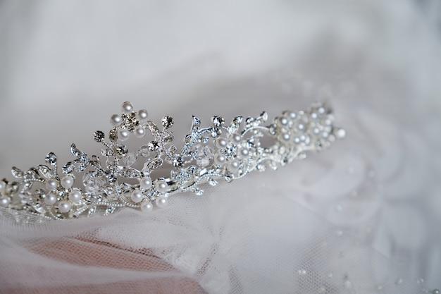 Piękna korona panny młodej jest na zasłonie, zbliżenie. dzień ślubu. rano panna młoda.