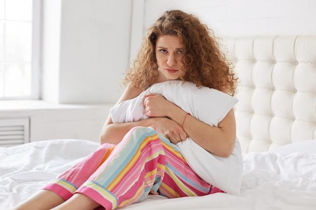 Piękna, kręcona kobieta w piżamie, trzyma białą poduszkę w dłoniach, czuje się sfrustrowana z powodu bólu brzucha, siedzi na wygodnym białym łóżku, jest chora. urocza młoda kobieta jest w rozpaczy z powodu bólu