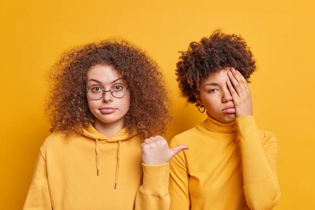 Piękna, kręcona kobieta wskazuje kciukiem na swoją znudzoną, sfrustrowaną przyjaciółkę, zastanawiając się, dlaczego jest przygnębiona, ubrana niedbale, na białym tle nad żółtą ścianą. koncepcja emocji i różnorodności ludzi
