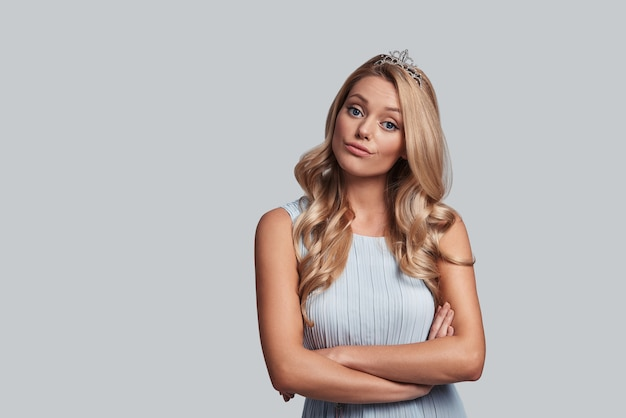 Piękna królowa. dumna młoda kobieta w koronie trzymająca skrzyżowane ręce i patrząca w kamerę, stojąc na szarym tle