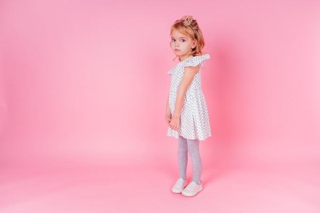 Piękna królowa w złotym crown.little zakupy dziewczyna w sukni mody księżniczki. ładne dziecko przygotowuje się do urodzinowego przyjęcia wielkanocnego na różowym tle w studio.