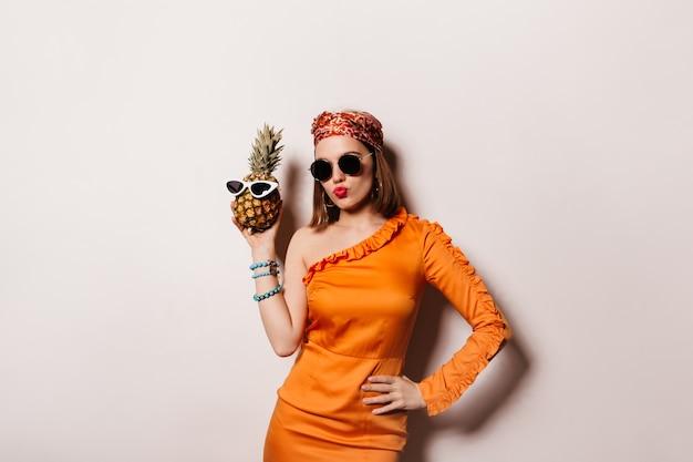 Piękna krótkowłosa kobieta w okularach przeciwsłonecznych i modnej pomarańczowej sukience nosiła okulary na ananasie.
