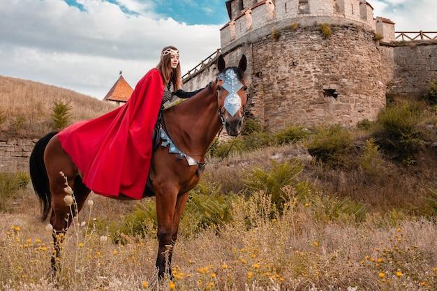 Piękna księżniczka w czerwonej pelerynie na koniu na tle wieży i kamiennego muru