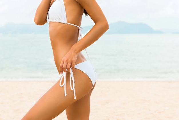 Piękna kształt kobieta w białym bikini swimsuit pozuje przy plażą