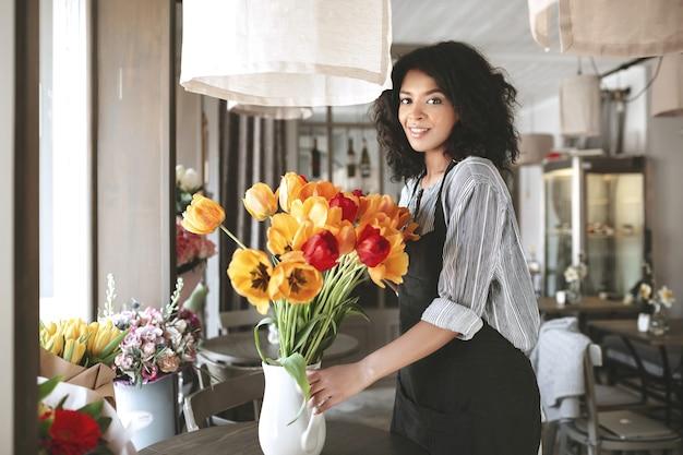 Piękna kwiaciarka w fartuchu tworząca wielki bukiet kolorowych tulipanów w wazonie. młoda dziewczyna afroamerykanów stojących z kolorowymi kwiatami