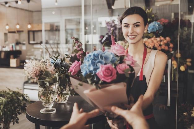 Piękna kwiaciarnia dziewczyna wysyła bukiet do kupującego