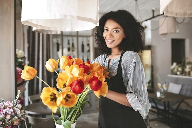 Piękna kwiaciarnia w fartuchu do pracy z kwiatami. młoda dziewczyna african american tworzenie bukiet tulipanów