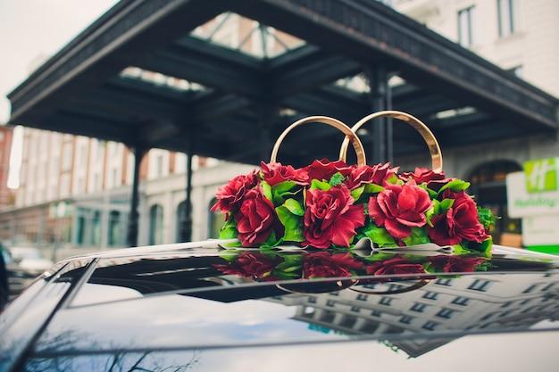 Piękna kwiat dekoracja na ślubnej samochodowej czapeczce z jeziornym tłem.