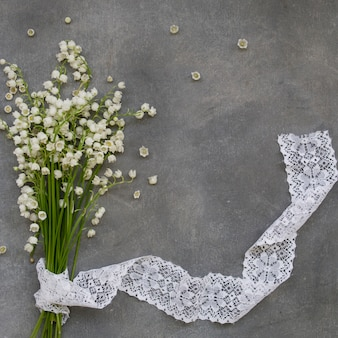 Piękna kwiecista rama z konwalii kwiatami na zmroku popielatym tle