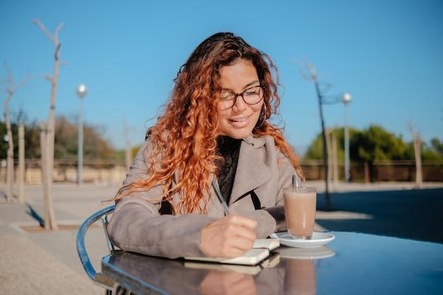 Piękna łacińska dziewczyna pije filiżankę kawy i ogląda telefon komórkowy, na metalowym stole na zewnątrz