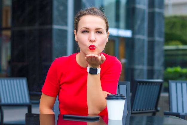 Piękna ładna dziewczyna, młoda ładna kobieta w czerwonym wysyłaniu, dmuchanie pocałunkiem z czerwonymi ustami, patrząc prosto w kamerę, siedząc w kawiarni na tarasie z filiżanką kawy, smartfon. całuję cię. pani na randce