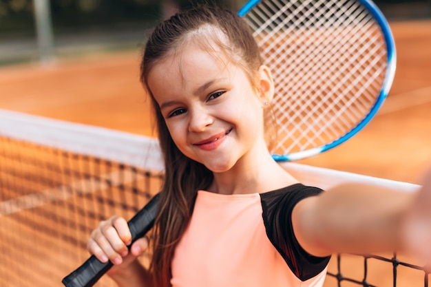 Piękna, ładna dziewczyna robi selfie z rakietą na korcie tenisowym