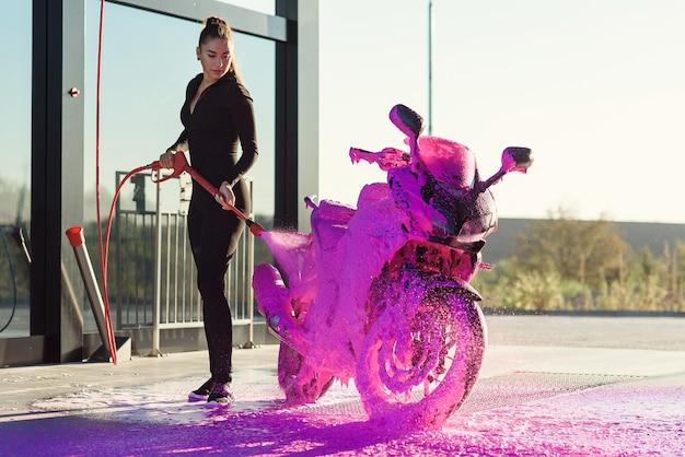 Piękna ładna dziewczyna w obcisłym, uwodzicielskim garniturze myje motocykl w samoobsługowej myjni samochodowej.