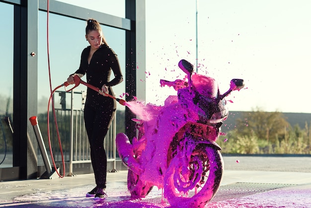 Piękna ładna dziewczyna w obcisłym, uwodzicielskim garniturze myje motocykl w samoobsługowej myjni samochodowej