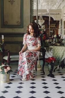 Piękna ładna dziewczyna w płaszczu sukienka koktajlowa z kwiatami pozowanie w luksusowym wnętrzu biblioteki. portret mody młodych modelek