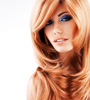 Piękna ładna kobieta z długimi rudymi włosami. portret młodej modelki z makijażem niebieskie oczy na białym tle na białej ścianie