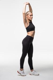 Piękna ładna młoda blondynka wykonuje różne ćwiczenia aktobatyczne rozciągające się na rękach i nogach na białym tle