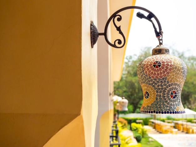Piękna lampa świetlna w stylu marokańskim, wisząca latarnia na zewnętrznej ścianie budynku.