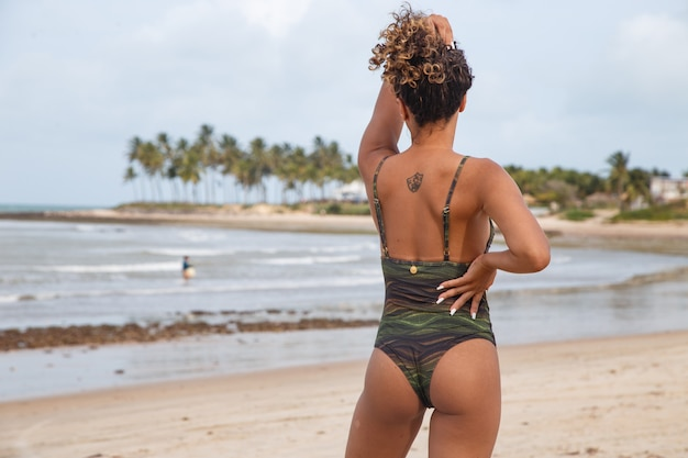 Piękna latynoamerykańska kobieta w bikini na plaży. młoda kobieta, ciesząc się letnimi wakacjami w słoneczny dzień, uśmiechając się i patrząc w kamerę