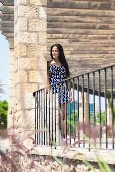 Piękna latynoska kobieta w błękit sukni opiera na ścianie podczas gdy patrzejący daleko od