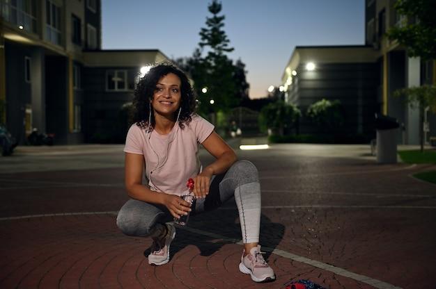 Piękna latynoska kobieta w stroju sportowym i słuchawkach kuca, trzyma butelkę wody i uroczo się uśmiecha, patrząc w bok. kobieta odpoczywa po treningu wieczorem