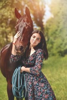 Piękna latynoska kobieta w sukience i jej piękny koń spacer po lesie. koncepcja miłości zwierząt. kocham konie