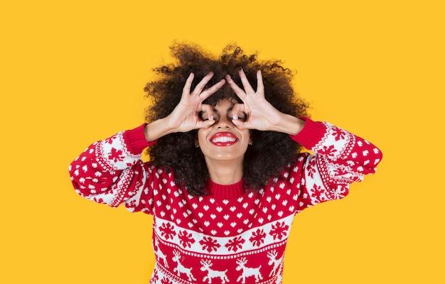 Piękna latynoska latynoska kobieta w świątecznych ubraniach i ok gestem w oczach, żółte tło