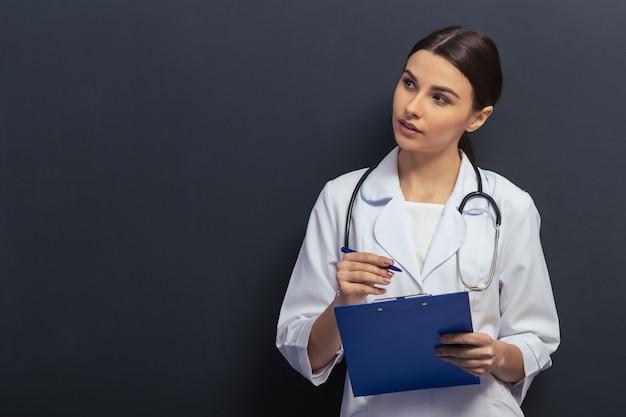 Piękna lekarka w białej medycznej sukni robi notatkom. copyspace