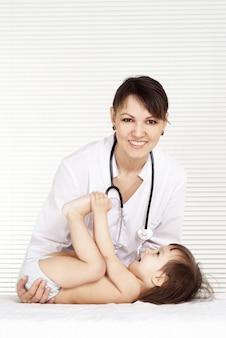 Piękna lekarka z małą dziewczynką w swoim gabinecie