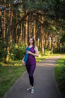 Piękna lekkoatletka w mundurze z matą do treningu stoi na ścieżce w parku