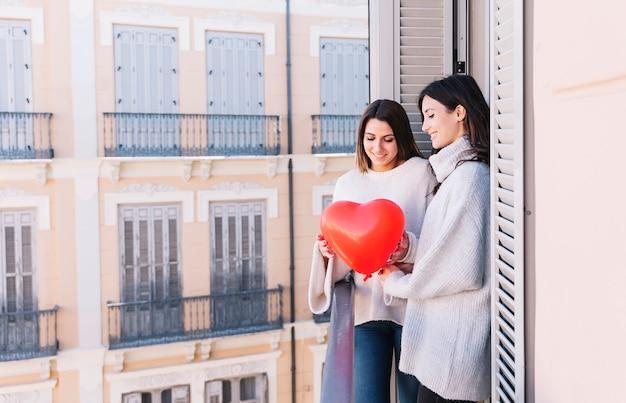Piękna lesbijska para z balonem na balkonie