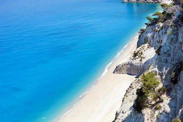 Piękna letnia biała plaża egremni nad morzem jońskim (lefkada, grecja) letni widok z najbliższej skały