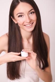 Piękna, ludzi, kosmetyków, skincare i zdrowia pojęcie, - szczęśliwa uśmiechnięta młoda kobieta stosuje śmietankę jej twarz