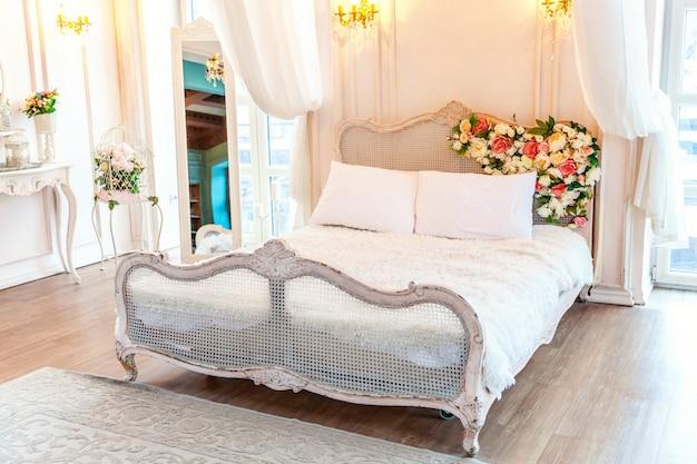 Piękna luksusowa klasyczna biała jasna, czysta sypialnia wnętrza w stylu barokowym z łóżkiem king-size, dużym oknem, fotelem i kompozycją kwiatową
