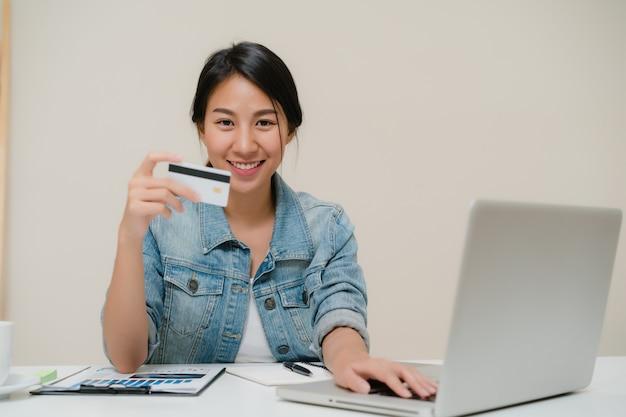 Piękna mądrze biznesowa azjatycka kobieta używa komputer lub laptop kupuje online zakupy kredytową kartą podczas gdy będący ubranym mądrze przypadkowego obsiadanie na biurku w żywym pokoju w domu.