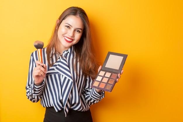 Piękna makeup artysty kobieta jest szczęśliwa na żółtym tle