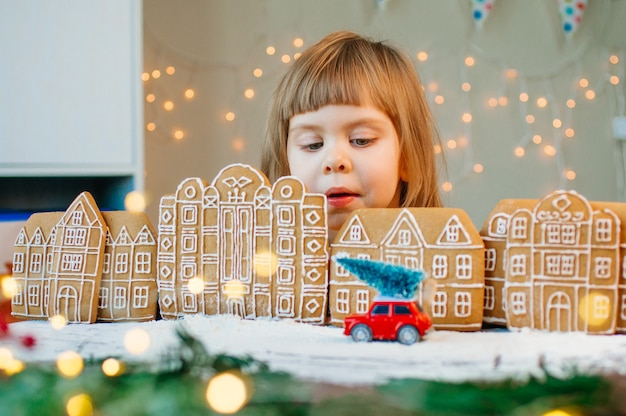 Piękna mała 3-letnia dziewczynka patrząc na samochodzik z choinką w miasteczku pierniki. selektywne skupienie się na dziewczynie.