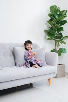 Piękna mała azjatycka dziewczyna bawiąca się na kanapie