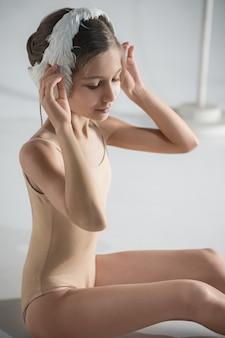 Piękna mała baletnica ubrana w biały łabędzi bandaż na głowie