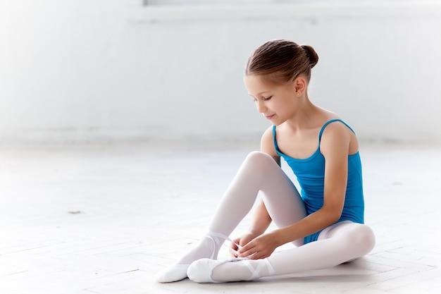 Piękna mała baletnica w niebieskiej sukience do tańca siedząc na podłodze i stawiając