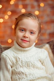 Piękna mała blond dziewczyna ono uśmiecha się przy nowym rokiem na tle choinka z niebieskimi oczami