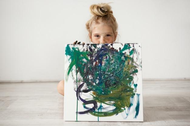 Piękna mała blondynka trzyma i ukrywa się przy dużym obrazie