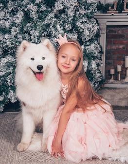 Piękna mała blondynka uśmiecha się z białym psem samoyedem przy noworocznym drzewie.